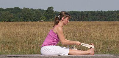 Yogaübung-Paschimottanasana-sitzende-Vorbeuge-mit-Gurt